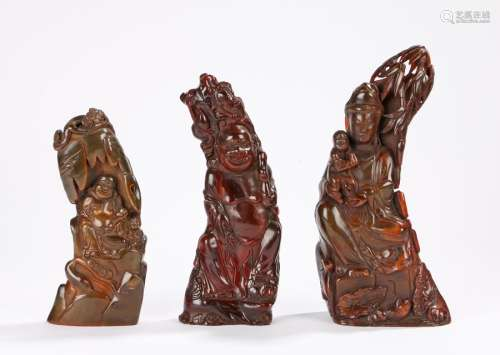 Three polished horn carvings depicting a mother and child and two smiling gentlemen, the largest