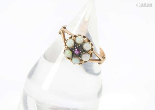 An early 20th Century gold and gem set ring, marked 585, with a cluster of opals centred by a red