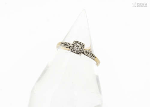 An art deco diamond solitaire ring, platinum set with diamond chip set shoulders on a yellow metal