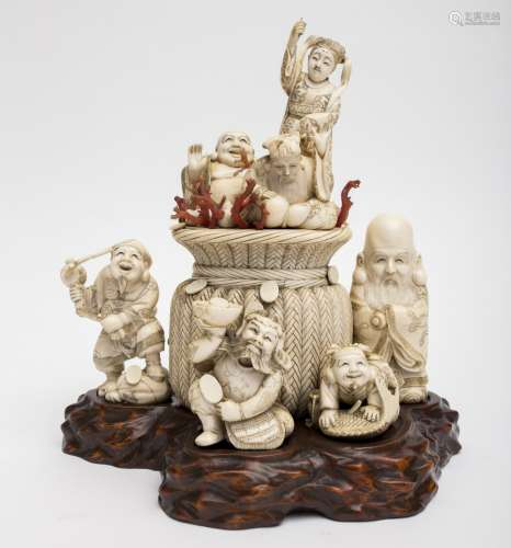 Rare group of okimono Ivory and coral on a boxwood stand carved as a boulder, representing the