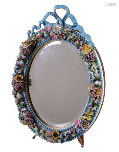 An English porcelain flower encrusted oval looking glass frame with wood easel stand, surmounted