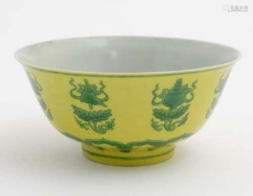 A Chinese bowl decorated with green auspicious motifs