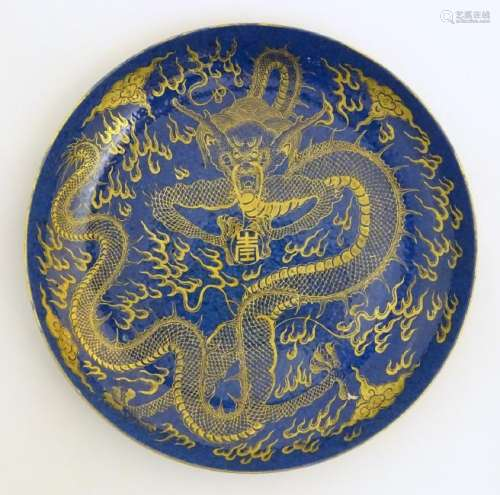 A Chinese dish decorated with a gilt dragon on a blue