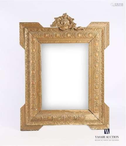 Miroir en bois mouluré sculpté et bronziné, il est…